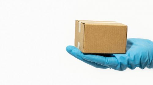 Delivery man holding cardboard box in rubber gloves. Online shopping and parcel delivery during Coronavirus COVID-19 pandemic. Copy space. Banner