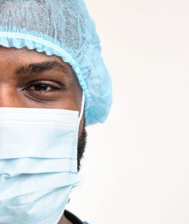 Half face portrait of african doctor with face mask